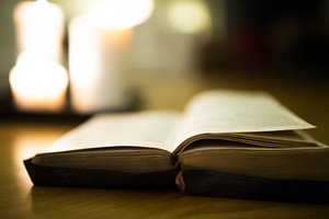 Close up of an old Bible laid on wooden floor, burning candles in the background