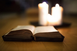 Close up of an old Bible laid on wooden floor, burning candles next to it