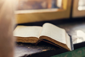 Close up of an old prayer book laid on windowsill