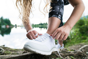 Close up of an unrecognizable young runner tying shoelaces, green nature