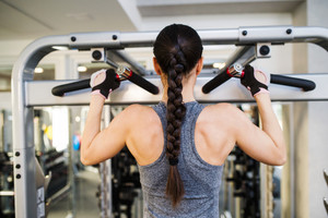 Close up of attractive fit woman flexing back muscles on cable machine, back view, rear viewpoint