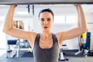 Close up of attractive fit woman in gym doing arms exercises on a machine