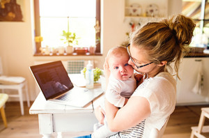 Close up of beautiful mother holding her baby son in the arms, kissing him, laptop and milk in the bottle laid on table