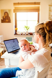 Close up of beautiful mother holding her baby son in the arms, laptop laid on table