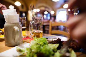 Close up of beer mug and meal laid on wooden table in restaurant.