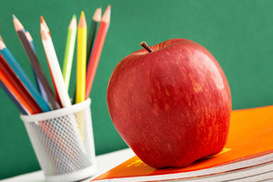 Close-up of big red apple on stack of copybooks with colorful pencils on background