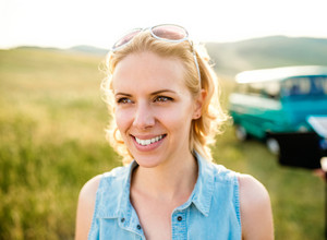 Close up of blond woman with curly hair in denim shirt in green sunny nature, old campervan.