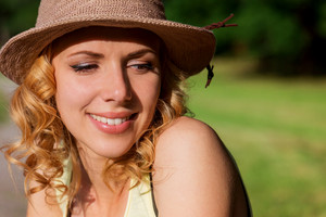 Close up of blond woman with curly hair in yellow singlet and hat in green nature. Sunny summer.