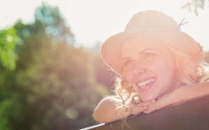 Close up of blond woman with curly hair with hat sitting on bench in green nature. Sunny summer.
