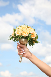 Close-up of bridal hand holding yellow rose bouquet on background of sky