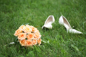 Close-up of bridal yellow rose bouquet on background of her white shoes on green grass
