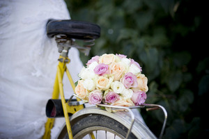 Close-up of bride in white wedding dress on retro bicycle