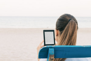 Close-up of brunette reading a book on the beach, view from the back, space for text