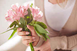 Close-up of bunch of pink lilies in female hands