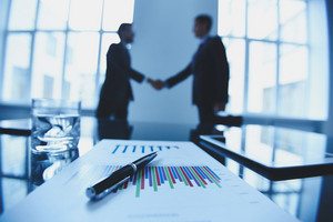 Close-up of business objects at workplace on background of partners handshaking