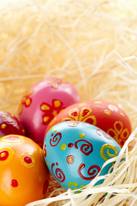 Close-up of colored and decorated Easter eggs in straw