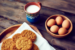 Close-up of cookies with eggs and cup of milk