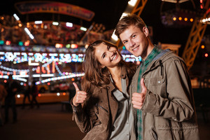 Close up of couple in amusement park. in warm clothes. looking at camera