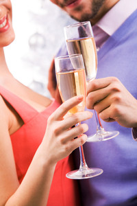 Close-up of couple with champagne flutes celebrating holiday