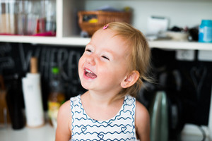 Close up of cute little happy girl at home laughing