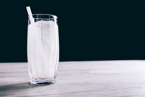 Close-up of empty glass with a straw from a smoothie on a black background