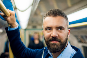 Close up of face of businessman with headphones travelling to work. Standing inside underground wagon, holding handhandle.