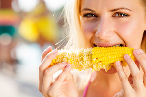 Close up of face of woman in bikini eating corn. Summer and heat.
