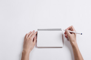 Close-up of female hand writing pen in a blank notebook on a white table