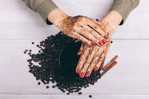 Close-up of female hands apply coffee scrub, top view