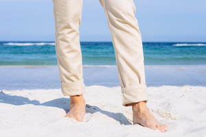 Close-up of female legs in beige pants barefoot on the beach. Walking along the coast on a sunny day.