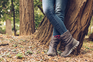 Close-up of female legs in jeans and boots in autumn park