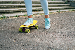 Close-up of female legs in jeans and sneakers riding a skateboard in the park
