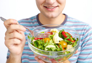 Close-up of fresh vegetable salad being eaten by man