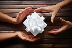 Close-up of gift box among two pairs of hands