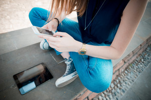 close up of hands and legs woman with tablet and smartphone in the street