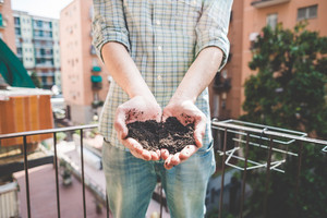 close up of hands holding soil on the balcony