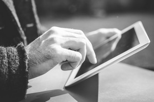 close up of hands man using tablet outdoor