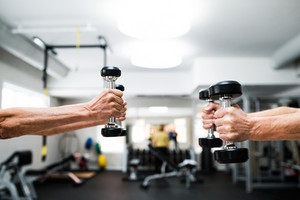 Close up of hands of senior couple in gym working out with weights