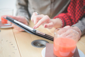 Close-up of hands touching digital tablet, informal businesswoman and businessman with cups of juice on table - business, work, technology concept