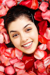 Close-up of happy female face above water surrounded by rose petals