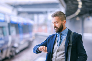 Close up of hipster businessman waiting at the train station platform, looking at watch on hand