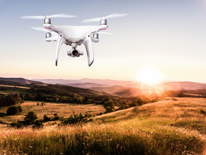 Close up of hovering drone taking pictures of green meadows and hills at sunset
