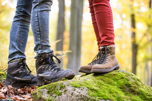 Close up of legs of unrecognizable man and woman in autumn nature standing on a rock covered with green moss. Hiking shoes.