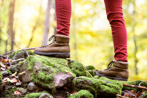 Close up of legs of unrecognizable woman in autumn nature standing on a rock covered with green moss. Hiking shoes.