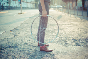 close up of legs shoes hipster man holding old bicycle wheel in the city