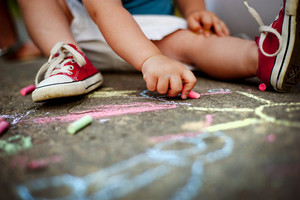 Close up of little boy in canvas shoes drawing with chalks on the sidewalk