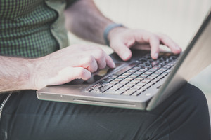 close up of man hands using laptop outdoor