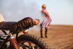 Close up of motorcycle wheel and flashlights with a man on the backgroud
