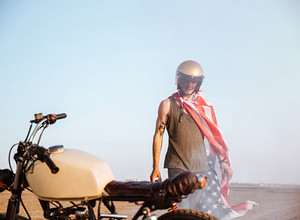 Close up of motorcycle with a man on the backgroud standing in desert
