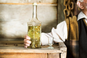Close-up of of bottle of herbal spirit held by an old man